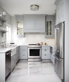 Modern Kitchen Design This gray u-shaped kitchen features a gray paneled hood flanked by antiqued mirrored kitchen cabinets and mounted against white and gray mosaic backsplash tiles over a stainless steel oven range. Grey Kitchen Cabinets, Kitchen Cabinet Design, Kitchen Tiles, New Kitchen, Kitchen Decor, Kitchen Grey, White Cabinets, Kitchen With Tile Floor, White Kitchen Flooring