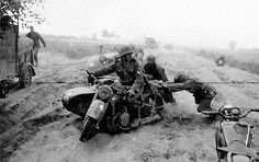 """Soldiers from Totenkopf Division struggle to move a BMW R12 motorcycle combination bogged down in a soft, sandy road during the drive on Leningrad in the early autumn of 1941. The motorcycle, driven by an SS-Rottenführer who is wearing the Iron Cross Second Class ribbon, is marked with the white Totenkopf emblem painted on the side of the front mudguard along with a white number """"23"""" on the side of the gas tank."""