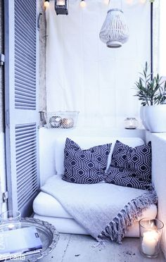 Turn a tiny balcony space into a holiday-styles haven with a large comfy chair, blankets and a white colour scheme.