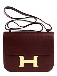 """Ca. 18 x 24 x 5 cm. Rotbraune Epsom-Ledertasche mit langem Schulterriemen, goldfarbenen Beschlägen und großem """"H""""-Klappverschluss. Innenraum mit einem..."""