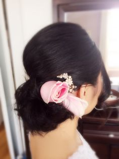 Shoulder length hair-up do with fresh pink roses.