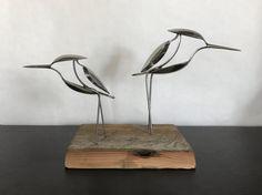 Shore vogels gemaakt van gerecycled gebruiksvoorwerpen en gemonteerd op teruggewonnen hout.