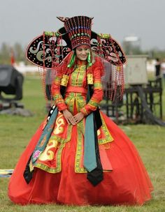 A woman dressed in traditional costumes of Mongolian ethnic group poses during the opening ceremony of the 2nd Ordos International Nadam Fair in Ordos City, north China's Inner Mongolia Autonomous Region. http://english.sina.com/life/p/2012/0827/500691.html