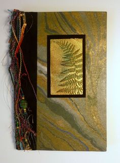 Notebook covered in metallic marbled paper with embossed fern embellishment.