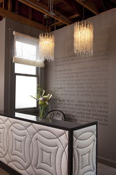 Exposed wood ceiling, wall paint color, die cut vinyl lettering, upholstered desk with nailhead trim, decorative lights to add more twinkle - positioned for a chic retail boutique, salon, or spa for young women