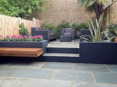 sandstone paving patio hardwood floating bench dark grey rendered walls london low maintenance garden dulwich west norwood clapham