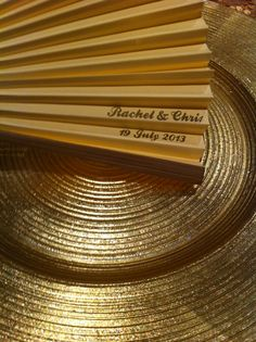 Gold glass charger plates & personalised paper fans at wedding  Www.littleweddinghelper.co.uk