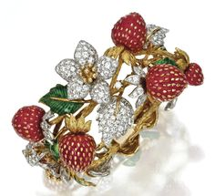 18 KARAT GOLD, PLATINUM, DIAMOND, CORAL AND ENAMEL STRAWBERRY BRACELET, DONALD CLAFLIN FOR TIFFANY & CO., CIRCA 1970 The textured gold vines supporting carved coral strawberries studded with gold seeds, accented by flowers and leaves set with round diamonds weighing approximately 9.00 carats, some leaves applied with translucent green enamel, length 6¾ inches, signed Tiffany & Co.