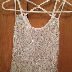 Sequins Tank Top This  tank top, has beautiful sequins on the front If you move in the light, it turns like a diamond color, and even shows like purple. But looking at it straight on, the sequins is a silver color.  Has cross straps in the back, and its totally white in the back. Its 60% cotton 35% polyester  Ans 5% spandex.  Can wear with jeans, a skirt, shorts, even dress pants. Its brand new without the tags. I never wore it, are tryed it on. Body Central Tops Tank Tops