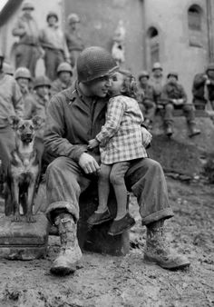 A sweet innocent moment in the middle of carnage: Pvt Alvin Harley of the 9th Armored Division gets a kiss from a little French girl in Abancourt, France on Valentine's Day 1945. Note the very serious puppy attending the instant. A wonderful photo indeed!