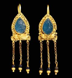 A PAIR OF ROMAN GOLD AND GLASS EARRINGS   Circa 2nd-3rd Century A.D.   Each drop-shaped, set with a blue glass and framed by a pair of twisted ribbons punctuated by granules, a bow below of sheet with incised grooves and voluted ends, a cluster of granules in the center, the lower edge with a beaded wire border from which is suspended three lengths of loop-in-loop chain, each terminating in a glass bead and a large and small hollow sphere, a hooked ear wire in back