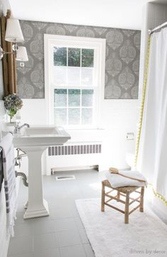 A budget bathroom remodel with ceramic tile floors painted gray and walls stenciled to look like wallpaper. Bathroom includes pedestal since, wood medicine cabinet, twin sconces, and tasseled shower curtain. #tile #paint #diy