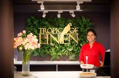 Welcome to Tropic Of Linen Boutique! Counter top & background with foliage and brass logo. TropicOfLinen