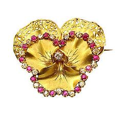 Fine Napoleon III 18K yellow gold pansy brooch, the upper large petals accented with a lacy pierced floral border and the lower petals with a row of alternating rose cut diamonds and antique cushion cut rubies. The gold surfaces have a matte finish that mimics the velvety texture of pansy blossoms. Delicate engraving brings out the veining on the lower petals.