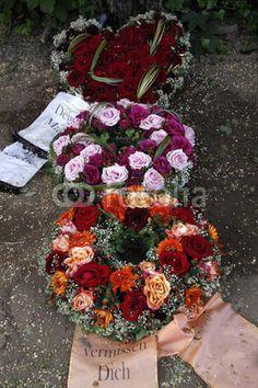 Blumen und Kränze auf einem frischen Grab