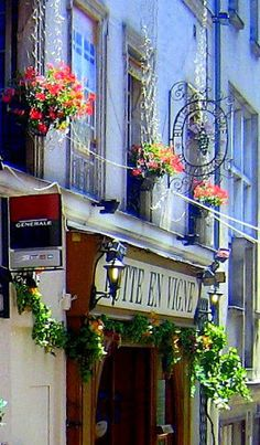 Fleurs trailing from pretty window boxes  ironcast lanterns - scrolled signage  and cobbled alleyways  all an integral part of that quai...