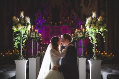 The bride and groom kiss at this Gorton Monastery wedding ceremony. The aisle is dressed with flowers and candlesticks - photo by tobiah tayo photography - available for commissions worldwide - www.tobiahtayo.com