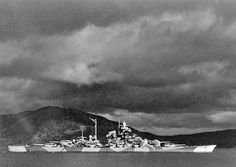 "DKM ""Tirpitz"" photographed in the Alta Fijord, Norway, probably in mid 1943. Tirpitz was the second of the Bismarck class battleships (8 x 38 cm [15 inch] guns, 42,900 tons, top speed 30 kts.) These ships had a great reputation, but the design was conservative, and they were not the equals of the US Iowa class, or the South Dakotas. Note the torpedo nets around Tirpitz. The nets would not protect Tirpitz from mining by British midget submarines here in Sept. 1943, which severely damaged her."