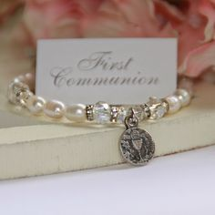 """This freshwater pearl and Swarovski crystal children's bracelet is accented with an antiqued First Communion charm. Bracelet measures: 6"""" Beautifully boxed for gift presentation. Handcrafted in the U."""
