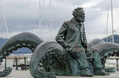 This monument in bronze honours the distinguished French writer Jules Verne, who mentioned the Bay of Vigo and the mythical treasures of Rande in one of the episodes of his book 20.000 Leagues Under the Sea. After publishing this book, the writer arrived at the city of Vigo in 1978 on board his yacht Saint Michel III. The sculture was donated by the Businesswoman's Association of Pontevedra on the centenary of the death of the writer. Leagues Under The Sea, Public Art, Business Women, Saints, Lion Sculpture, This Book, Death, Bronze, City