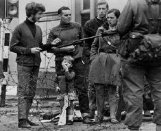 This press photo illustrates what is called 'The Troubles' in Northern Ireland. It is not dated, but was probably taken in the late-1960s and early-70s. Batricades like this were established to separate the Catholic and Protestant sections of Belfast. Notice the British soldier's rifle with a fixed bayonet and the little boy with his toy cowboy rifle.