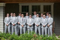 Groom with 12 groomsmen all in light gray suits with pale purple ties and sunglasses. | Jessica Williams Photography