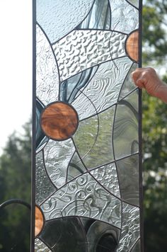 This large custom stained glass panel makes quite a statement, yet speaks softly by using very little color. Textures, design, and brown accent glass are woven by design into a contemporary collage. Commissioned Stained Glass Window Decorations from Windsong Glass Studio add visual interest to your home that you'll enjoy for years. This panel for a new home construction represents the New Adventures for the family. Why named 'New Adventures'? This panel is all about motion. As each brown…