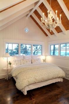 cream colored bedding makes this bedroom light and airy but the dark floors keep in cozy