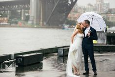 Love still shines even when it's raining!  @mmphotosaus #mmphotos #rainydays #rain #umbrella #sydneyweddingphotographer #husbandandwife #justmarried #cityofsydney #sydneyharbourbridge #sydneyharbour #puddles #love by mmphotosaus http://ift.tt/1NRMbNv