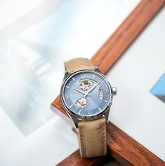 Add a striking blue dial to your summer wardrobe when you choose the new 42mm Jazzmaster Open Heart Auto.