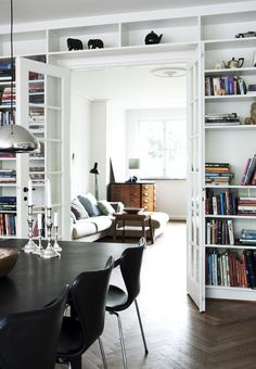 A contemporary duplex living/dining with bookcases around the french doors