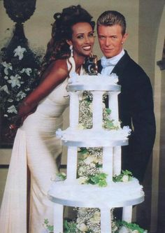 Iman and David Bowie on their wedding day with a four tiered cake