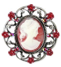 Beauty and the bouquet! Pinned on your blouse or gown, our Floral Cameo Brooch in Red will make you feel as if you've stepped out of the pages of a Victorian romance novel.Oval cameo features a woman's profile in ivory on an antiqued red background – all surrounded by delicate floral filigree bedazzled with faux stone centers.Alloy and resin brooch measures approximately 1.75 x 1.75 inches with pin on back. Imported