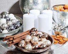 christmas decoration  Ein Adventskranz der anderen Sorte: Hier wurden vier große Blockkerzen mit eleganten Silberschalen zu einem modernen Adventskranz arrangiert. Orangenscheiben, Zimtstangen und Christbaumschmuck in Pastell- und Greigetönen vollenden das moderne Weihnachtsensemble