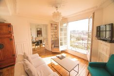 Entire home/apt in Paris, France. Lovely sunny and typical Parisian flat in the center of Paris with balcony and beautiful view, on floor (with elevator) of a traditional Parisi. Paris Apartment Rentals, Paris Apartments, Parisian, Balcony, Flooring, Living Room, Mirror, Furniture, Beautiful