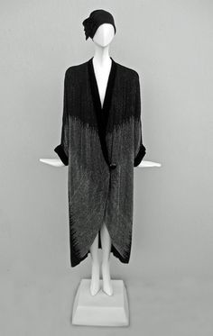 Paul Poiret. Opera Coat. circa 1924. Stunning cocoon evening coat of black georgette, hand beaded overall in lines of black beads switching to gray translucent beads with a geometric ragged edge formed at the color change.