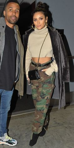 Celebrity Street Style    Picture    Description  Shay Mitchell hit up a basketball game looking sporty and chic wearing camouflage trousers with a cropped turtleneck. The cute accessories— leather belt, chain bag, high-heel boots, and gold hoop earrings—took the look to the next level.     https://looks.tn/celebrity/street-style/celebrity-street-style-shay-mitchell-hit-up-a-basketball-game-looking-sporty-and-chic-wearing-camouflag/