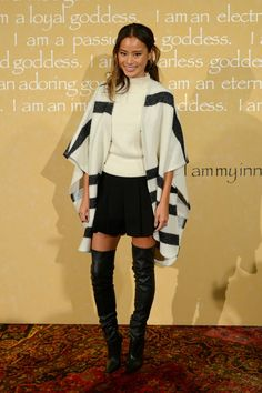 Jamie Chung wears a high-neck sweater, striped poncho, miniskirt, and thigh-high leather boots