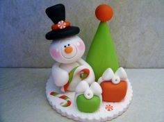 A whimsical snowman is seated next to his little Christmas tree. He has with him candy canes, peppermint candies and two presents!   This is an original design that was handcrafted from polymer clay. The piece measures approximately 2 1/2 tall. All parts have been secured with liquid polymer for increased strength.     Not a toy...not suitable for young children.