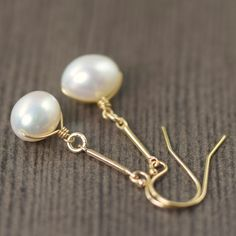 These earrings feature AAA white freshwater pearls wire wrapped by hand using gold filled wire. Each earrings dangle freely at 1.5 inches from a gold filled bar off of gold filled earwires shopsouthpaw.com