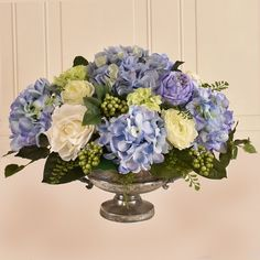 Blue and purple faux hydrangeas are nestled with stems, leaves, and berries in this artificial arrangement. Use this ensemble to anchor a garden-chic dining room tablescape while its ceramic planter complements crisp white plates and table cloths. Home Flowers, Faux Flowers, Silk Flowers, Church Flowers, Funeral Flowers, Flowers Garden, Fresh Flowers, Colorful Flowers, Blue Hydrangea Centerpieces