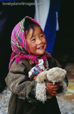 Tibetan girl smiling and holding teddy. Nam-Tso, Tibet, China. More