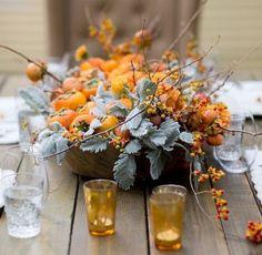 décoration table d'automne - arrangement de grenades orange, baies et feuilles dans un bol au centre de la table