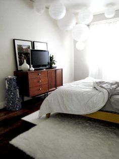 Picture frames behind the bedroom TV add depth; white lanterns are also comfy and casual White Lanterns, Paper Lanterns, Hanging Lanterns, White Vases, Apartment Design, Apartment Therapy, Thing 1, Dresser As Nightstand, Next At Home