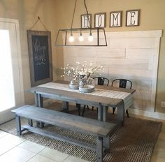 Farmhouse shabby chic dining table. Rustic wood picnic-style table with bench seat. Caged 3-light billiard-style chandelier.