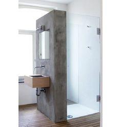 Do lado oposto do chuveiro, a pia e o espelho se apoiam em uma parede de cimento queimado
