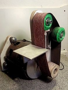 Belt Sander - Belt sander constructed using roller skate wheels to support the sanding belt and driven with a washing machine motor.