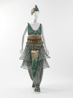 Paul Poiret | Fancy Dress Costume | c. 1911 Early in the twentieth century Diaghilev's Russian dance company, Ballets Russes, performed in Paris—reigniting the taste for orientalism in Europe with its exotic sets and costumes. As this ensemble illustrates, Poiret excelled in recontextualizing western dress with fantastical eastern influence. He was also a maverick modernist in creating a stir, taking promotion of his inventive ensembles to new levels with his infamous spectaculars. This…