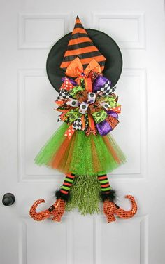 A whimsical witch sitting on a lime green sparkled broom. She's dressed in an orange and lime green tutu with black/orange/green Raz witch leg with glittered orange boots. A large Terri Bow in six dif