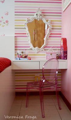 Como um dos desejos da Nanda era uma penteadeira de princesa, que não cabia ali, criei o console com gavetas. Para demarcar os espaços, inseri o papel de parede listrado no cantinho de beleza, um espelho provençal e uma cadeira Elizabeth Mini. Ela amou! Agora tinha uma penteadeira digna de uma princesa!